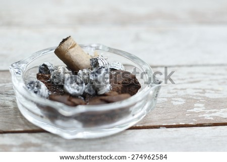 cigar, its ash in ashtray on wooden table. finished smoked cigar, cigar ash  in an glass ashtray on wooden table. - stock photo