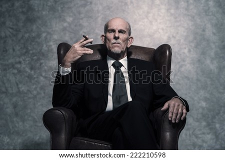 Cigar smoking senior businessman with gray beard wearing dark suit and tie. Sitting in leather chair. Against grey wall. - stock photo