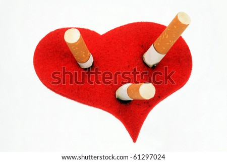 Cigaret stubs in heart on a white background - stock photo