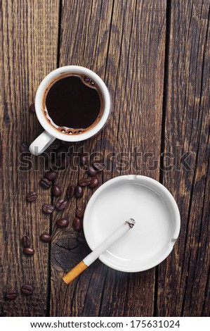 Cigarette and coffee on vintage wooden background. Top view - stock photo