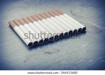 Cigarette arrangement on green grungy wood surface, tobacco industry background