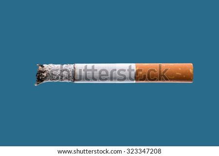 Cigarette burning on light blue background, smoke addiction concept - stock photo