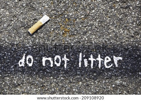 cigarette butt on a tar road with the written massage: do not litter - stock photo