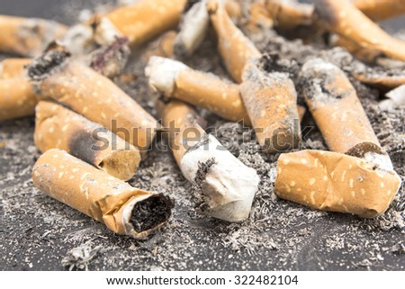 Cigarette butts in a pile close-up. - stock photo