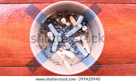 Cigarette Butts In Ashtray Sand cover with crosshairs - stock photo
