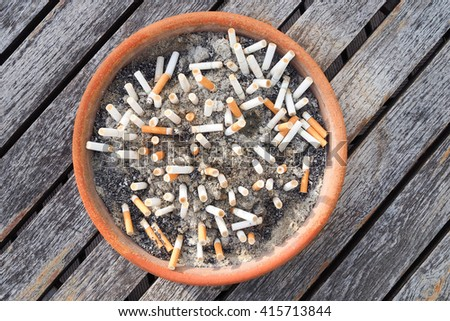 Cigarette butts in the ashtray on wood table background. The concept of World No Tobacco Day in 31 May, stop smoking, do not smoke, quit smoking, protect your health and other. - stock photo