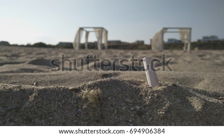 Cigarette butts in the sand on the beach, dirty beach