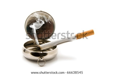 cigarette in an ash-tray on a white background - stock photo