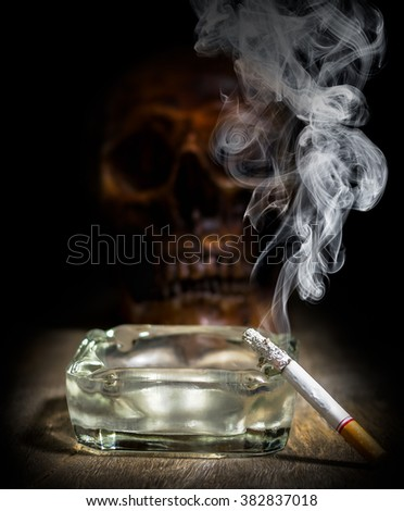 cigarette in ashtray on table and skull background