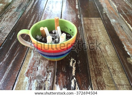 Cigarette in ashtray shaped cups of coffee on wood table. - stock photo