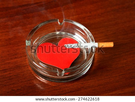 Cigarette in Ashtray with Heart Shape on the Table - stock photo