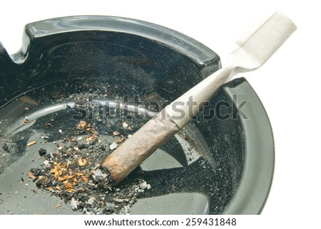 cigarette in dirty black ashtray closeup on white - stock photo