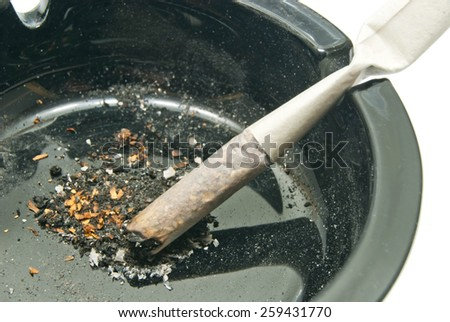 cigarette in dirty black ashtray on white background closeup - stock photo