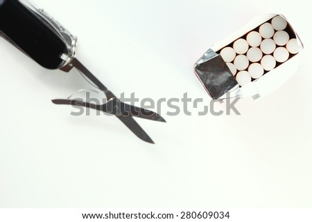 Cigarette in paper packaging and scissors with cutting action appearance represent the tobacco concept related idea. - stock photo