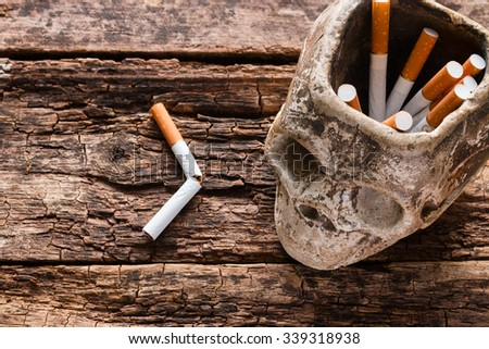 cigarette in the ashtray in the form of a skull smoking kills concept - stock photo