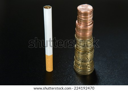 Cigarette next to stack of coins, close-up - stock photo