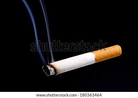 Cigarette on black background - stock photo