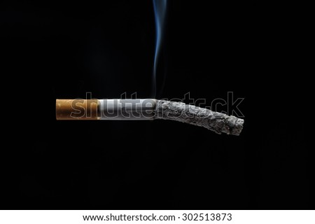 Cigarette on black background, free space for text.