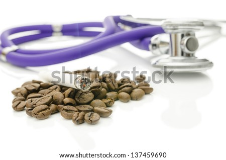Cigarette on coffee beans with stethoscope in background. Addiction concept. - stock photo