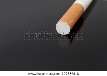 Cigarette on the black glass with reflection. - stock photo