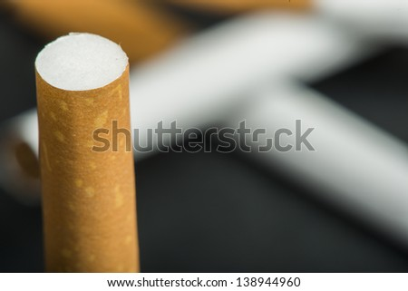 Cigarette on the foreground and many cigarettes on a background