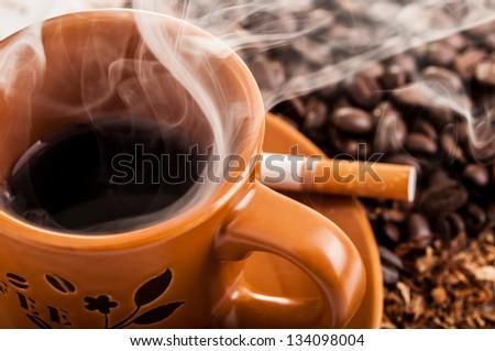 Cigarette, smoke and a cup o coffee - stock photo