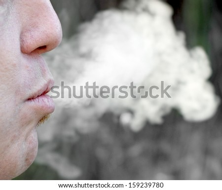 cigarette smoke and chain-smoker in a moment of relaxation - stock photo