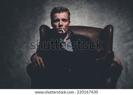 Cigarette smoking retro fifties cool business fashion man wearing black suit. Sitting in leather chair. Gray wall. - stock photo