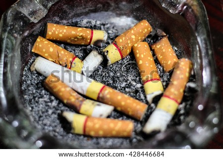 Cigarette stub./ Abstract blurred burning cigarette butt left in an ashtray. - stock photo