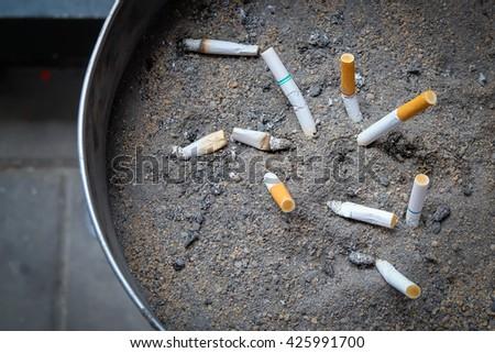 Cigarette stub in ash tray - stock photo