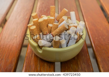 cigarette stub in dirty ashtray on wood table - stock photo
