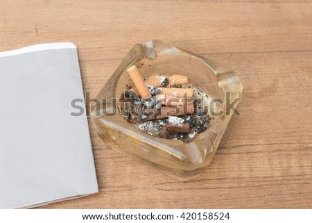 cigarette with an ashtray on the wood table, Many filter cigarette a small ashtray, no smoking concept. - stock photo