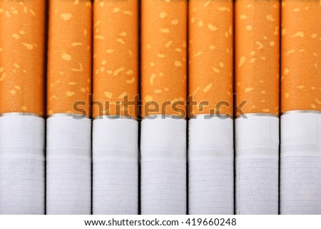 Cigarette with an orange filter lie close to each other close up - stock photo