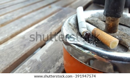 cigarette with ashtray on wood table . Selective focus - stock photo