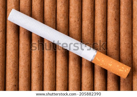 Cigarette with brown filter on dark cigarettes close up - stock photo