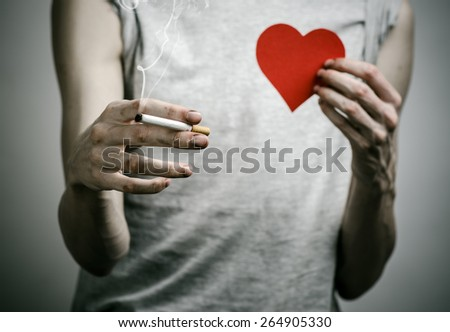 Cigarettes, addiction and public health topic: smoker holds the cigarette in his hand and a red heart on a dark background in the studio - stock photo