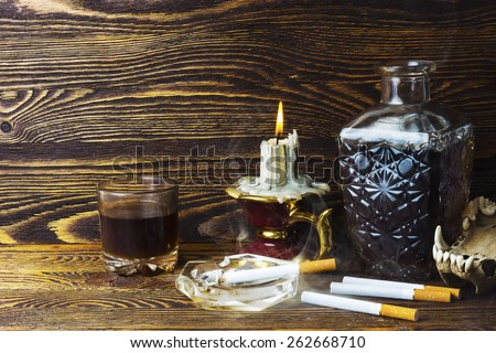 Cigarettes and alcohol candle - stock photo