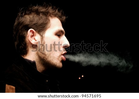 cigarettes are bad, nicotine is addictive handsome man breathing out cigarettes smoke - stock photo
