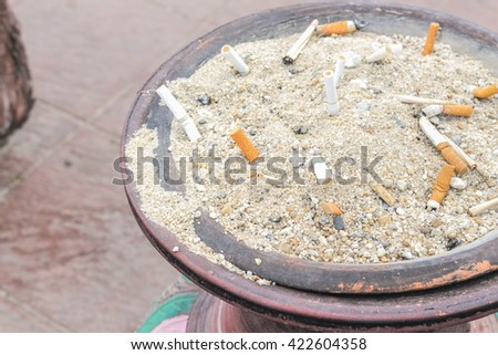 Cigarettes butt in sand ashtray.( select focus front Cigarettes and Blur blurred a background) - stock photo
