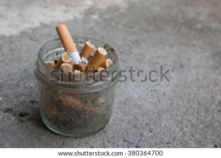 cigarettes in a transparent glass close-up. Cigarettes closeup with copy space. World no tobacco day background. Stop quit smoking background. - stock photo