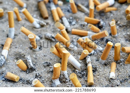 Cigarettes in outdoors ashtray with sand closeup image - stock photo