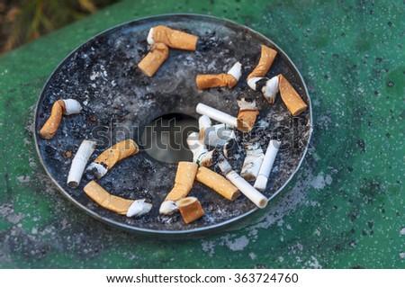 Cigarettes in outdoors green rusty ashtray  - stock photo