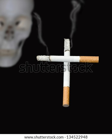 Cigarettes in the form of a cross against a human skull - stock photo
