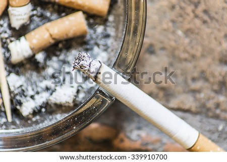 cigarettes on an ashtray with one still smoking - stock photo