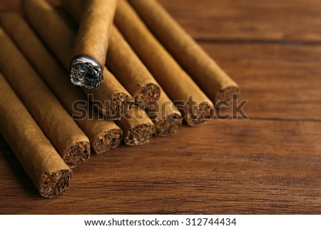 Cigars and burnt one with ash on wooden background - stock photo