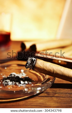 Cigars and burnt one with ash on wooden table, closeup - stock photo