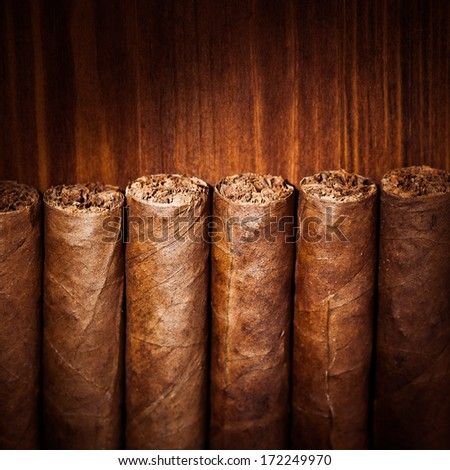 cigars on wooden background, closeup view - stock photo