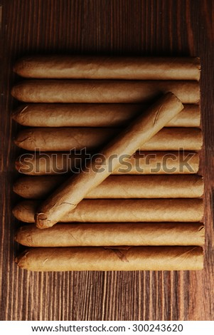 Cigars on wooden table, top view - stock photo