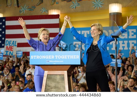 CINCINNATI, OHIO, USA - JUNE 27, 2016: Hillary Clinton and Elizabeth Warren on stage holding hands up during a campaign event at the Museum Center.