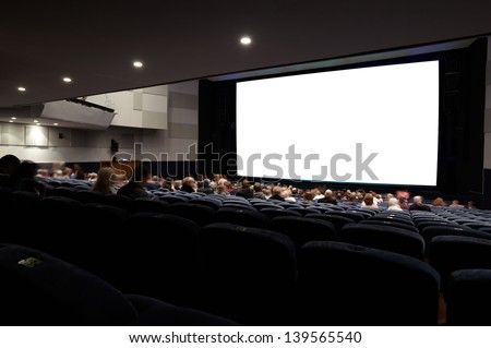 Cinema auditorium with people in chairs watching movie. Ready for adding your own picture. Diagonal perspective view. - stock photo